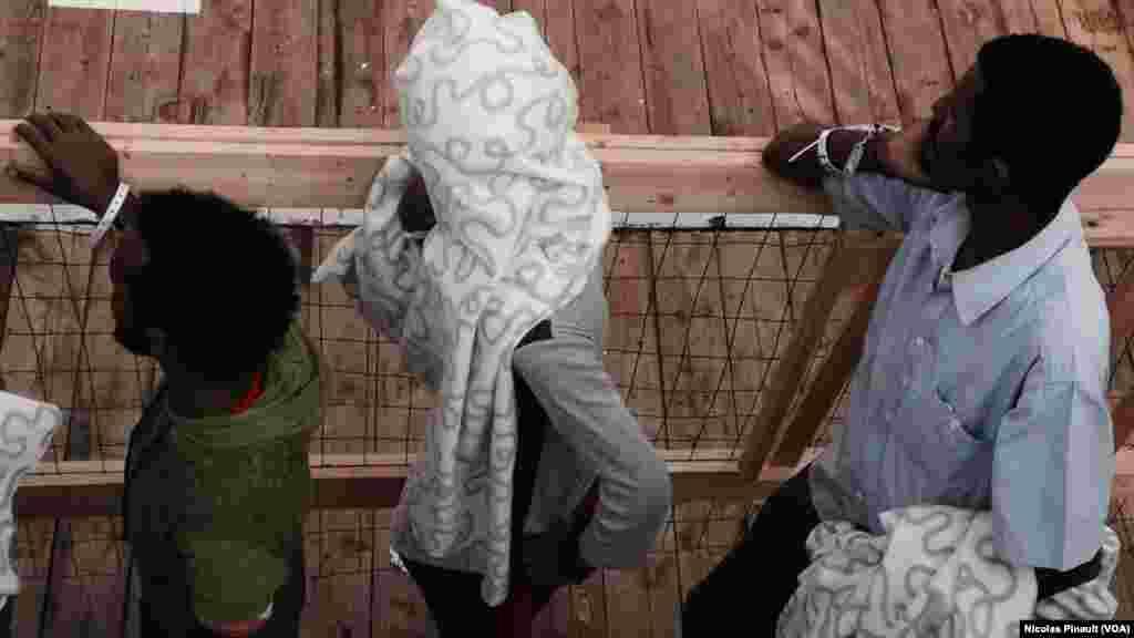 """Des migrants érythréens attendent de débarquer du """"Siem Pilot"""" à Messine, Sicile, 6 ocotbre 2015 (Nicolas Pinault/VOA)."""