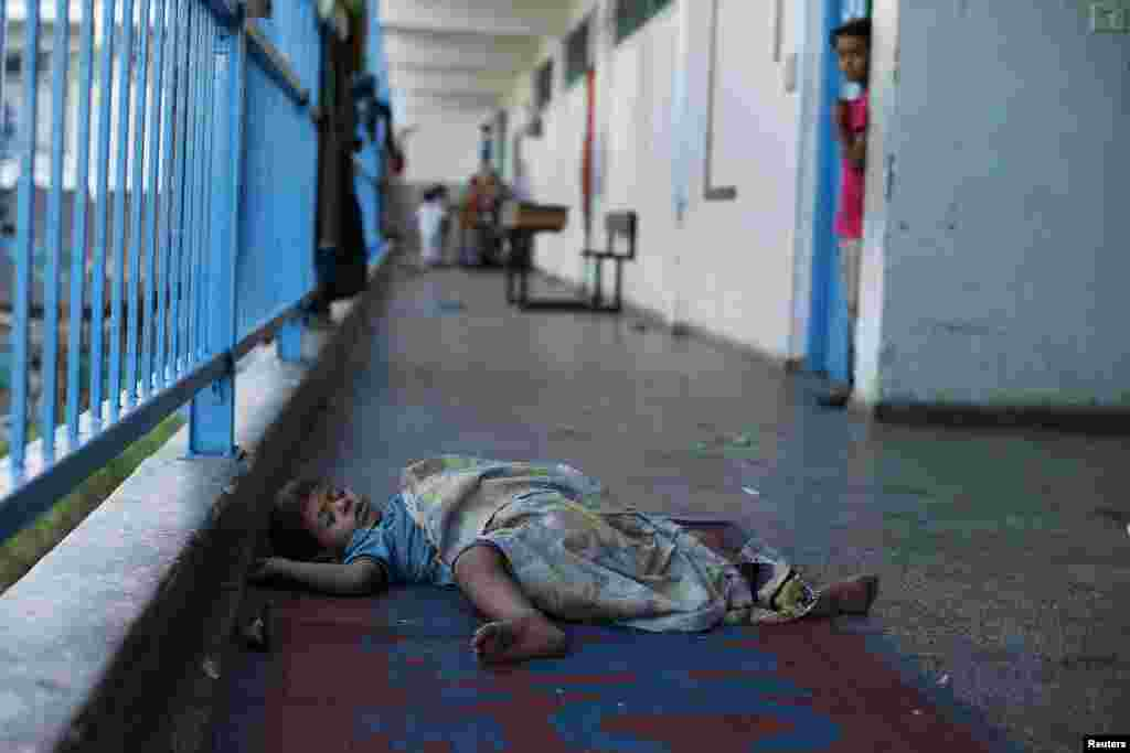 A Palestinian boy sleeps at a United Nations-run school that shelters Palestinians displaced by the Israeli offensive, in Beit Lahiya town, in the northern Gaza Strip, Aug. 12, 2014.