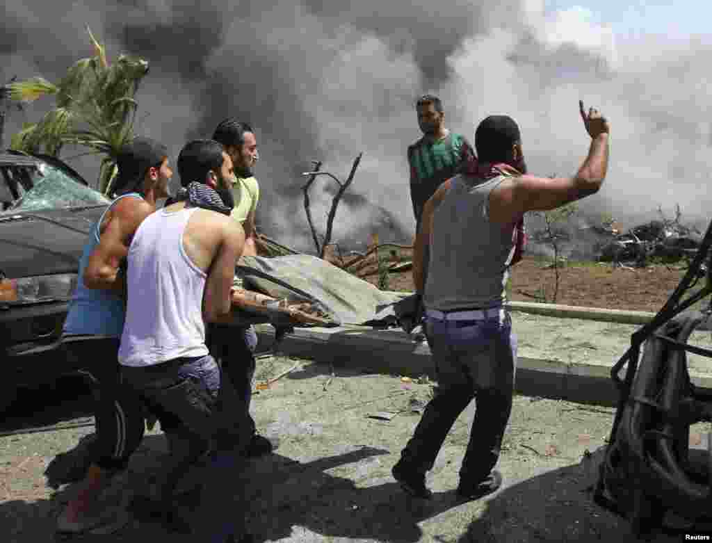 People carry a body outside one of two mosques hit by explosions in Lebanon's northern city of Tripoli, August 23, 2013.