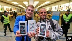 First customers of the Apple store in Oberhausen< Germany, are all smiles with their new iPhones on Sept. 20, 2013.
