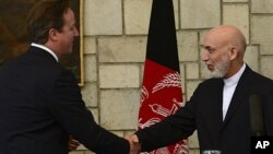 Afghan President Hamid Karzai, right, shakes hands with British Prime Minister David Cameron during a press conference at the presidential palace in Kabul, Afghanistan, June 29, 2013.