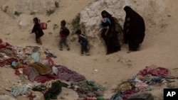 In this March 14, 2019, file photo, Women and their children who left the besieged Islamic State-held village of Baghouz, Syria, scramble over a rocky hillside to be checked by U.S-backed Syrian Democratic Forces. (AP Photo/Maya Alleruzzo, File)