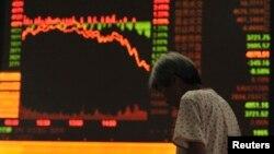中国安徽省阜阳市的一名投资者站在股票交易所的电子屏幕前(2015年7月27日)