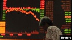 Seorang investor di Fuyang, Anhui, tampak lesu mengamati monitor indeks saham China yang kembali merosot.
