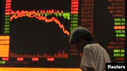 An investor stands near an electronic board showing stock information in a brokerage house in Anhui, China July 27, 2015. China stocks plunged more than 8 percent, their biggest one-day drop in more than eight years. (REUTERS/Stringer)