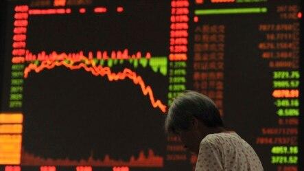 一位投资者站在安徽省阜阳市的股市电子板前(2015年7月27日)