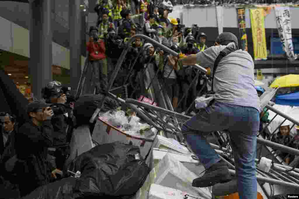 A pro-democracy protester lifts barricade reinforcements up onto an escalator near the government headquarters in Hong Kong's Admiralty district, December 1,2014.