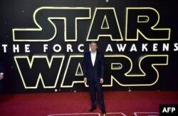 """Bob Iger, CEO Disney, berdiri di depan poster """"Star Wars: The Force Awaken"""""""