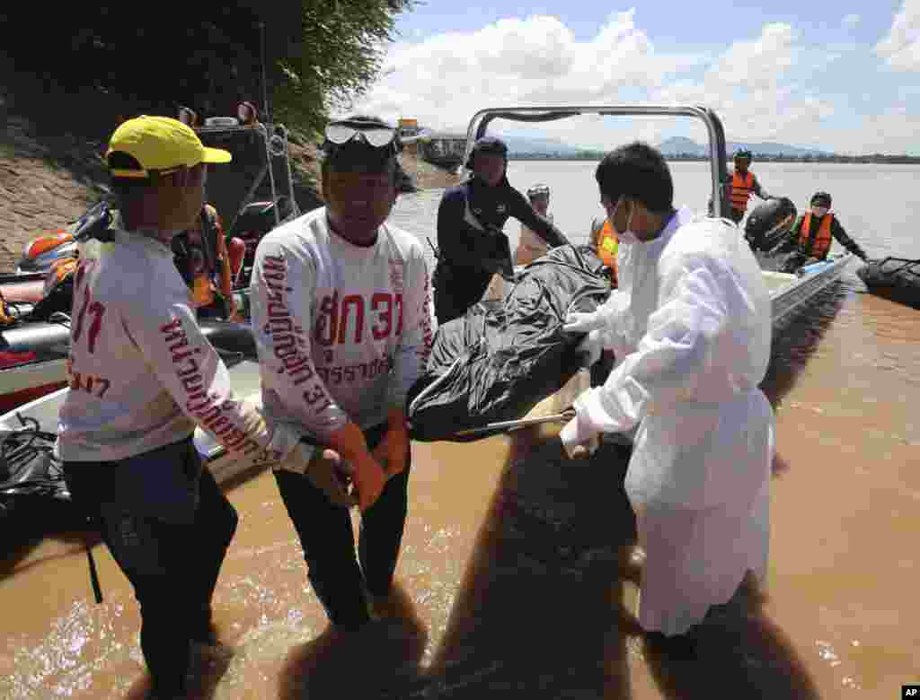 Thai rescuers unload the body of a plane crash victim from a boat in Pakse, Laos, Oct. 18, 2013.