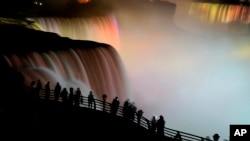 FILE - The American side of Niagara Falls and Horseshoe falls are lit up to celebrate the birth of the Duke and Duchess of Cambridge's son, George Alexander Louis. as people gather along the railing, July 23, 2013.