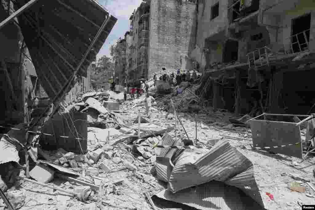 Men gather at a site hit by what activists said was a barrel bomb dropped by forces loyal to President Bashar al-Assad, in al-Qarlaq, Aleppo, May 29, 2014.