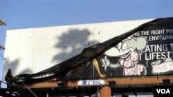 Un trabajador de la ciudad de LA removiendo una pancarta publicitaria que se alega fue alterada por el esténcil de Banksy.
