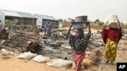 Quelques passants traversent des débris laissés par une explosion à Maiduguri, Nigeria, 8 juin 2017.