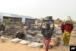 FILE - People walk through the debris at a camp for people displaced following an explosion by Islamist extremists, in Maiduguri, Nigeria, June 8, 2017.