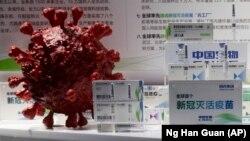 ARHIVA - Primerci kineske vakcine protiv Kovida 19 pored 3D modela koronavirusa na sajmu u Pekingu, u septembru 2020. (Foto: AP/Ng Han Guan)
