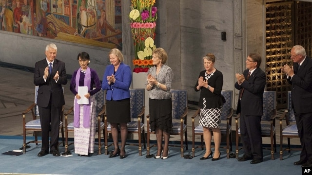 Burmese opposition leader Aung San Suu Kyi, on the podium, second from left, receives standing ovations the Norwegian Nobel Committee her speech at the Peace Nobel Prize lecture at the city hall in Oslo, Saturday, June 16, 2012.