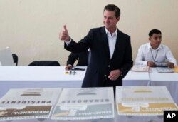 In this photo released by Mexico's presidential press office, Mexico's President Enrique Pena Nieto gives a thumbs up to photographers after voting during general elections in Mexico City, Sunday, July 1, 2018.