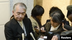 A Public Relations staff of JGC Corp answers reporters at its headquarters in Yokohama, in this photo taken by Kyodo, January 16, 2013.