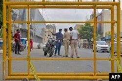 Polisi menghentikan pengendara motor di sebuah pos pemeriksaan selama pemberlakuan kembali karantina di tengah pandemi Covid-19 di Bangalore, India, 15 Juli 2020.