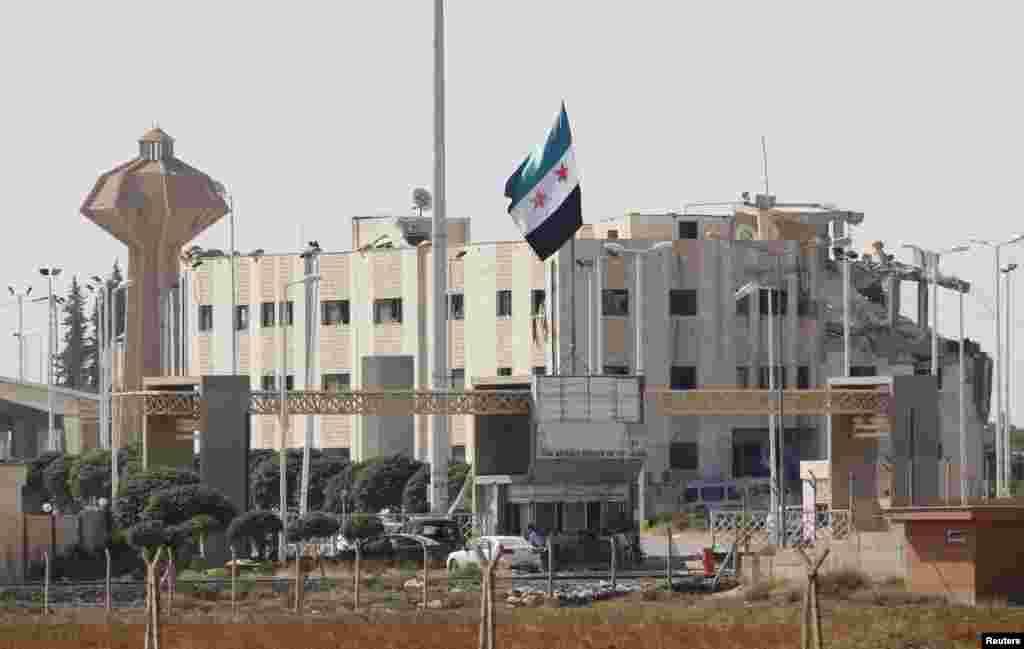 ترک شام سرحدی گذرگاہ پر واقع شام کے تباہ شدہ کسٹم ہاؤس پر باغیوں کا پرچم لہرا رہاہے
