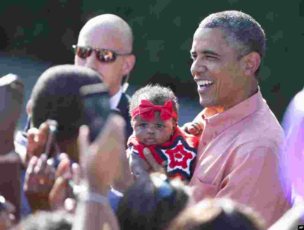 President Barack Obama holds a baby as he greets members of the military and their families during a Fourth of July celebration on the South Lawn of the White House in Washington, July 4, 2013.