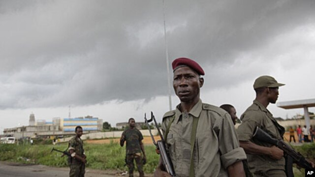 Soldiers allied with Alassane Ouattara stand in a road in the Youpougon neighborhood of Abidjan, Ivory Coast, Sunday, April 10, 2011