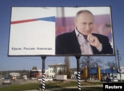 "FILE - A billboard with a portrait of Russian President Vladimir Putin is displayed on a street in Kerch, Crimea, April 7, 2016. The board reads: ""Crimea. Russia. Forever."""