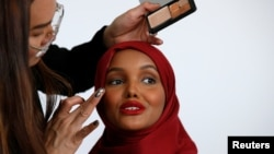 Fashion model and former refugee Halima Aden, has her makeup applied during a shoot at a studio in New York City, Aug. 28, 2017.