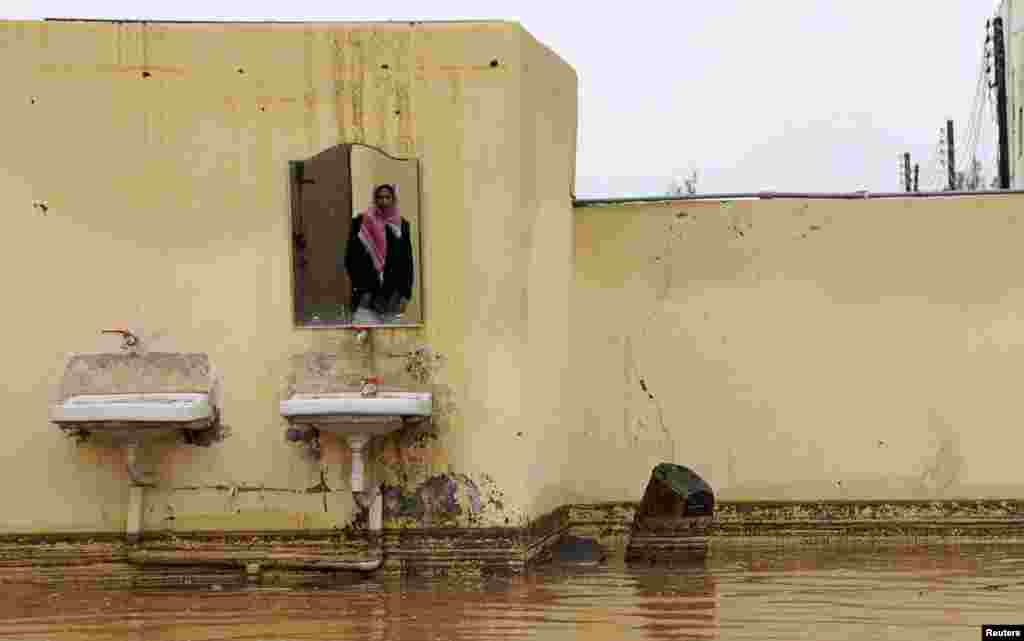 A Saudi man is reflected in a mirror in his flooded home after heavy rain in Tabuk, 1500 km (932 miles) from Riyadh, Saudi Arabia.