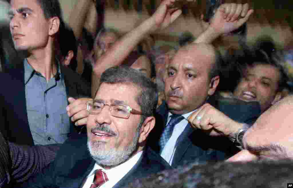Mohammed Morsi and his supporters celebrate his victory at his campaign headquarters in Cairo, June 18, 2012.