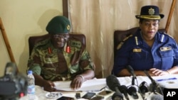 Zimbabwe army spokesperson Colonel Overson Mugwisi, left, addresses a press conference with police spokeswoman Charity Charamba, at Police General Headquarters in Harare, Zimbabwe, Nov. 27, 2017.