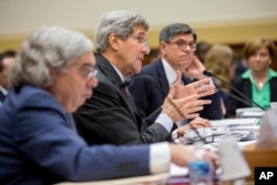 Secretary of State John Kerry, center, flanked by Treasury Secretary Jacob Lew, right, and Energy Secretary Ernest Moniz, testifies on Capitol Hill in Washington, Tuesday, July 28, 2015.