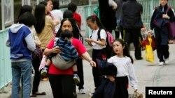 Một phụ nữ tay bồng tay dắt trẻ em bên ngoài một trường học ở Hong Kong