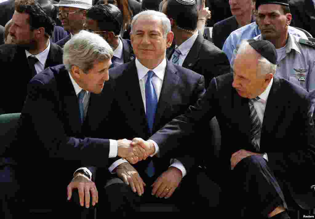 Israeli President Shimon Peres shakes hands with U.S. Secretary of State John Kerry as Prime Minister Benjamin Netanyahu sits between them during a ceremony marking Israel's annual day of Holocaust remembrance, at Yad Vashem, Jerusalem, April 8, 2013.