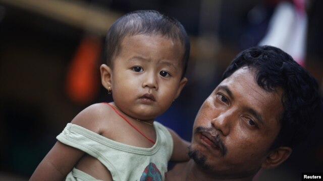 A migrant worker from Burma holds his daughter in front of their house in the port town of Mahachai, near Bangkok, September 24, 2011.