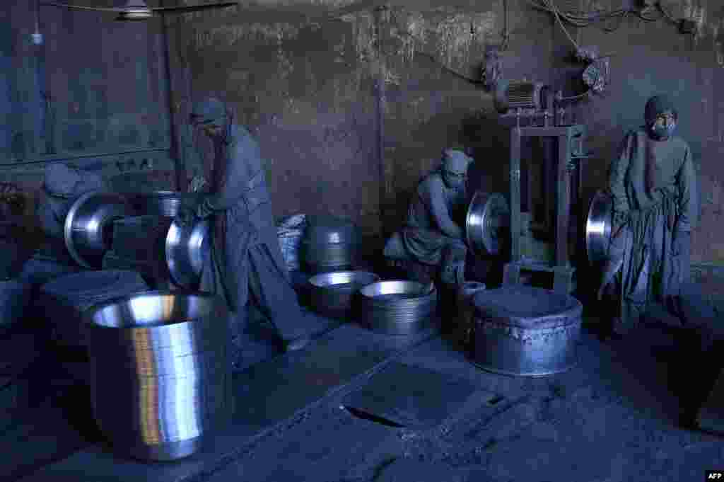 Afghan laborers polish metal pots at an aluminum factory in Herat.