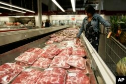 FILE - A shopper looks over pork products at a Costco store in Mountain View, Calif.