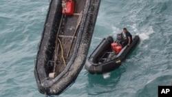 Penyelam Angkatan Laut Indonesia menunggu di sekoci mereka setelah menyelam untuk mengangkat ekor pesawat AirAsia QZ8501 di Laut Jawa, Kamis (8/1).