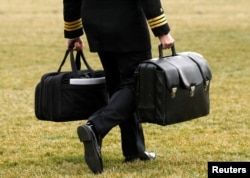 "FILE - A military aide, carrying the ""football"" containing launch codes for nuclear weapons, accompanies U.S. President Donald Trump onto Marine One upon Trump's departure from the White House in Washington, Feb. 3, 2017. Contrary to what Trump tweeted, he has no physical button to initiate a nuclear launch."