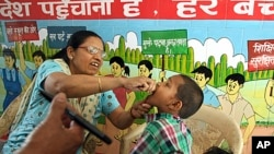 A health worker gives polio vaccine to a child at a school in New Delhi, India, April 7, 2013.