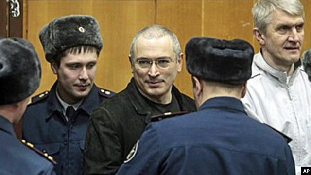 FILE - Mikhail Khodorkovsky, center, and his co-defendant Platon Lebedev, right, are escorted to a court room in Moscow on December 27, 2010.