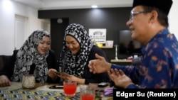 Tengku Shawal, a royal descendant, talks as his daughter Tengku Puteri (L) and his sister Tengku Intan (C) reminisce over old family photos at Intan's home in Singapore August 21, 2020. (REUTERS/Edgar Su)