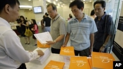 FILE - A staff distributes copies of the prospectus and brochures for the IPO of Alibaba, for the first day public offering at a local Hong Kong bank.