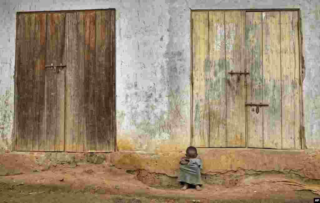 Seorang anak laki-laki Uganda duduk di depan rumahnya di desa Kyanukuzi, dekat Masaka, Uganda.