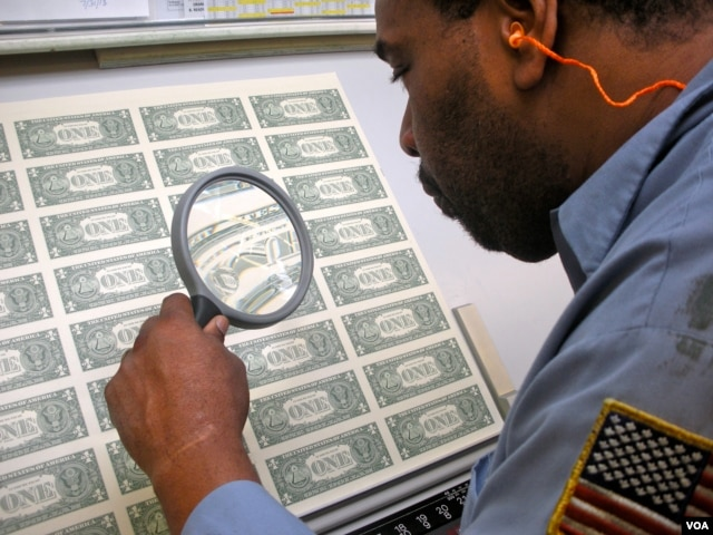 A worker at the Bureau of Engraving and Printing examines sheets of US currency before they are made into wallet-ready bills. (J. Taboh/VOA)