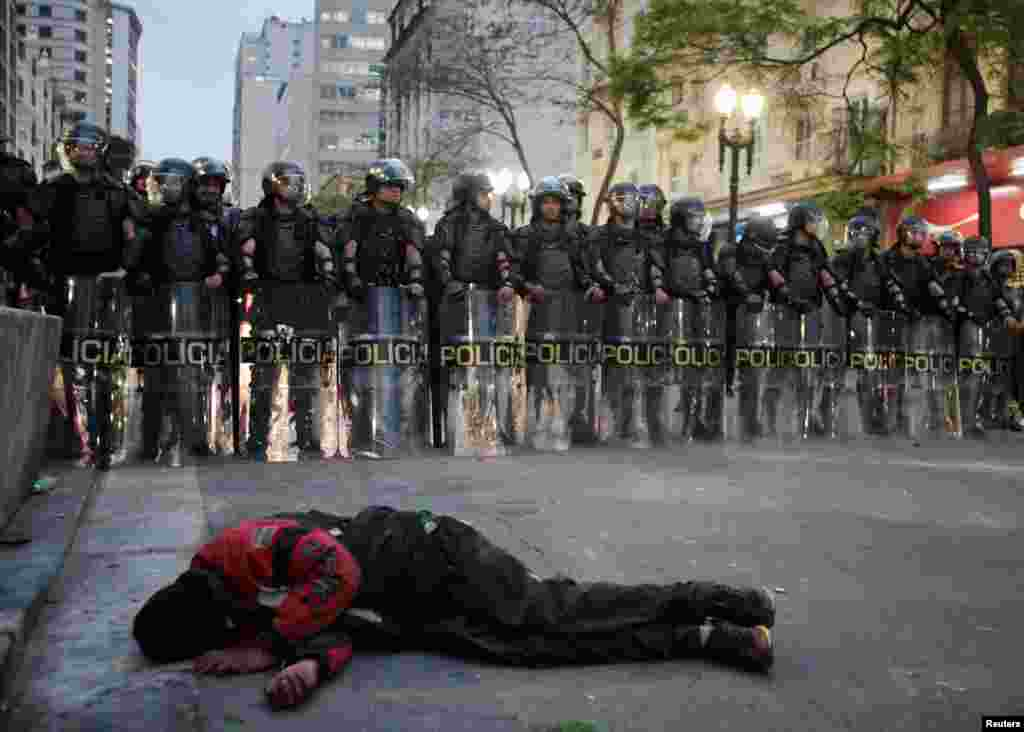 A homeless man sleeps as riot police face off against members of Brazil's Roofless Movement during a protest against their forced eviction from an abandoned building they were occupying, in downtown Sao Paulo, Sept. 16, 2014.
