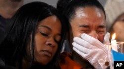 民众于12月3日为加州圣贝纳迪诺郡枪击案死难者举行的烛光守夜中一名妇女悲伤哭泣。