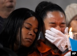FILE - A woman cries during a candlelight vigil for shooting victims on Thursday, Dec. 3, 2015.
