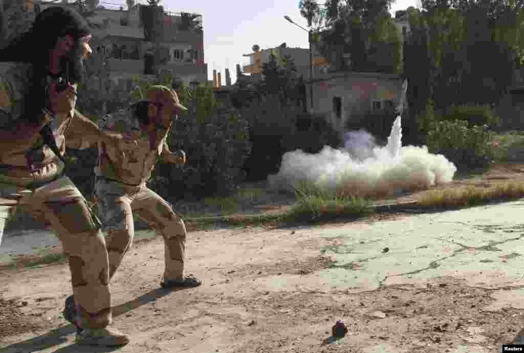 Members of the Free Syrian Army react as they fire a rocket in Deir al-Zor, June 16, 2013.