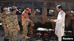 Petugas keamanan Pakistan mengumpulkan bukti-bukti serangan bom atas kereta api penumpang di kota Sibi, Baluchistan, Pakistan (8/4).